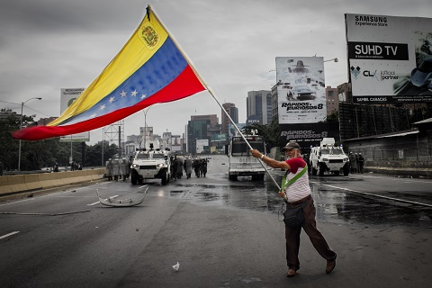 man in the street with a venezuela flag>The International Swaps and Derivatives Association (Isda), a committee that regulates derivatives, announced on 16 November that the government and Petr�leos de Venezuela, S.A (PDVSA), the state oil firm on which the economy relies, were in default. This announcement triggered credit default swaps (CDSes), which function as insurance contracts for bonds, allowing CDS holders to be compensated. Yet the value of derivative contracts compensated in this case is small compared to what Venezuela and PDVSA owe in outstanding bonds � about USD250 million by PDVSA and USD1.3 billion by Venezuela. Earlier this month, U.S.-based ratings agency <a href=